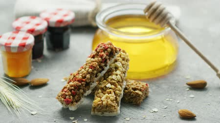 oat flakes : Sweet cereal bars on gray surface with jar of golden honey and small containers of marmalade