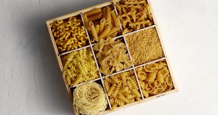 pişmemiş : Top view of wooden box with sections filled with various types of raw macaroni and pasta on white surface Stok Video