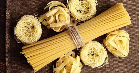 makarony : From above shot of tied bunch of raw spaghetti and pasta composed on canvas napkin