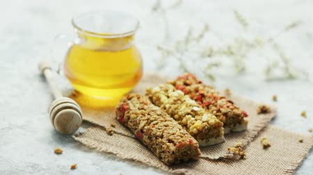 muesli : Composed few cereal bars on canvas napkins with glass jar of golden honey near Stock Footage