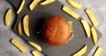 fries : Top view of fresh burger with golden bun and fries composed around in circle on board
