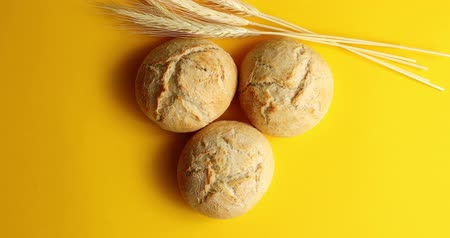 дрожжи : Top view of arranged round buns of crispy golden bread on yellow background with ears of wheat