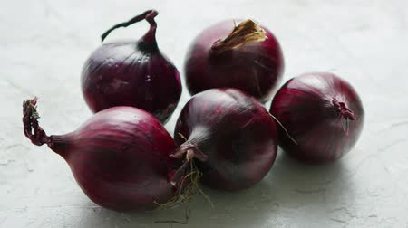 white onion : Closeup shot of unpeeled bulbs of red onion lying on white table surface in daylight