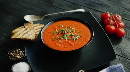 servido : From above view of tomato soup in black bowl sprinkled with herb served with crisp bread on wooden background