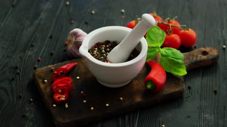 zátiší : From above view of white mortar and pestle with spices surrounded by pepper and tomatoes on chopping board on wooden background