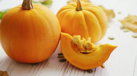 pumpkin pieces : From above view of yellow ripe pumpkins placed on wooden table Stock Footage