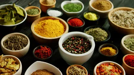 natural spicy : From above view of many little bowls with different kinds of spices laid on wooden background