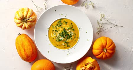 polvilha : From above view of pumpkin soup sprinkled with herb in white plate surrounded by little pumpkins on white background Vídeos