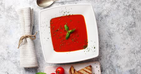 zupa : From above view of red tomato soup in white plate served with crisp bread and tablespoon on gray background