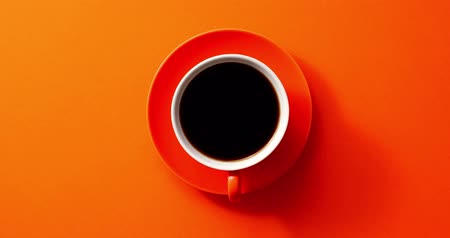 odstín : From above view of cup with black coffee placed on orange background