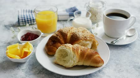 marmelada : Torn soft and delicious croissant on white plate served with coffee and orange juice and marmalade on marble table