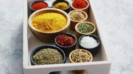 curcuma : From above of small wooden tray box with composed bowls of various aromatic spices on table