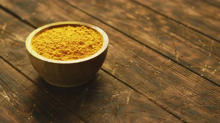 curcuma : Closeup shot of small round wooden bowl filled with bright colored orange turmeric spice composed on shabby wooden table