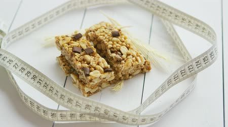 изюм : Homemade rustic granola bars with dried fruits on white wooden background. Fit concept with measure tape. Стоковые видеозаписи
