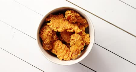 pergamen : From above shot of bucket full of tasty fried chicken wings standing on white lumber tabletop Dostupné videozáznamy