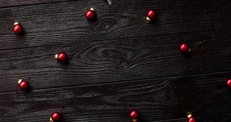 comemoração : From above shot of tiny red Christmas beads lying on surface of dark timber tabletop Vídeos