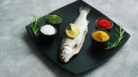 seasonings : Assorted aromatic spices lying on ceramic plate near fresh trout on surface of stone tabletop