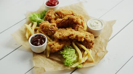 pergamen : Small bowls with assorted sauces and pile of palatable fried chicken wings lying on parchment paper on white wooden tabletop Dostupné videozáznamy