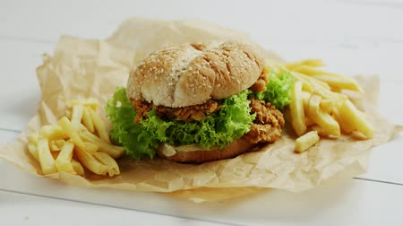 utěšený : Closeup shot of yummy French fries and tasty chicken burger lying on parchment paper on white timber tabletop
