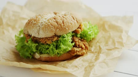 parşömen : Closeup shot of delicious chicken burger lying on parchment paper on white timber tabletop