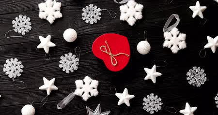 lays : From above view of white beautiful Christmas decorations and present in red box in shape of heart on wooden background Stock Footage