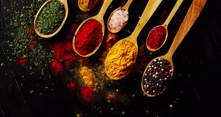 picante : From above view of different sort of colorful spices placed in spoons on wooden background