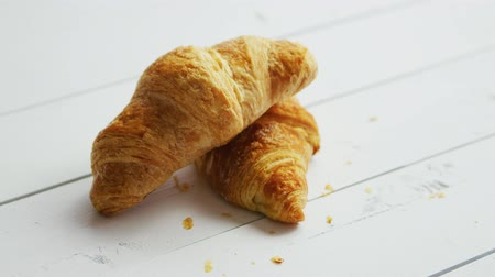 utěšený : Closeup shot of two delicious fresh croissants lying on one another on surface of white wooden table