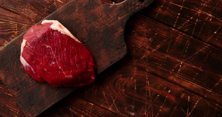 dilimleri : From above view of piece of raw meat laid on cutting board on wooden background Stok Video