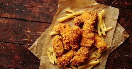 chicken pieces : From above view of fried pieces of meat and potatoes laid on paper napkin on wooden background