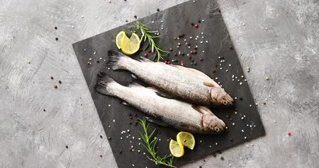 окропляет : From above view of fresh trout decorated with slices of lemon and herb placed on board on gray background Стоковые видеозаписи