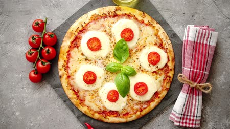 olasz konyha : Homemade pizza with tomatoes, mozzarella and basil. Top view with copy space on gray stone table.