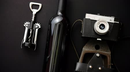slate : Red wine bottle, corkscrew and old photo camera on black matte background. Top view with copy space Stock Footage