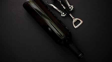 şişeler : Red wine bottle and corkscrew on black matte background. Top view with copy space Stok Video