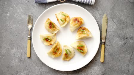 pierogi : Fried dumplings with meat filling sprinkled with fresh chive on a white plate. Top view on gray stone background