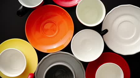 sortimento : Empty colorful modern ceramic plates and cups collection. Various of dishware over black background. Top view Vídeos