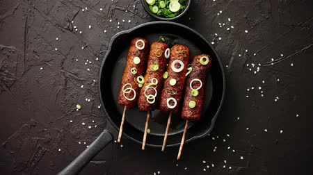 shish : Barbecued turkey kebab decorated with fresh onion and chive in frying pan, top view. Black stone background.