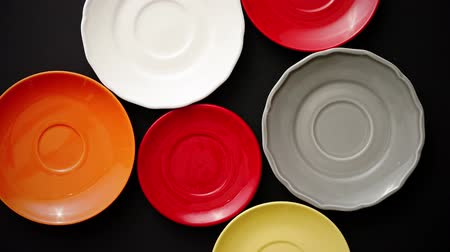 serving board : Colorful empty plates and saucers over black background. View from above