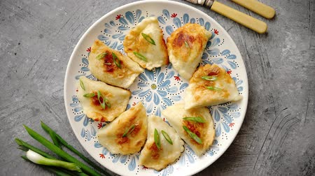 pierogi : Fried dumplings with meat filling sprinkled with fresh chive on a blue colorful plate. Top view on gray stone background Stock Footage