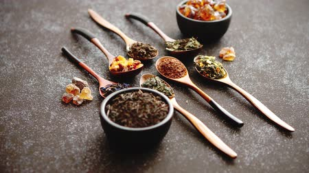 hibiscus tea : Spoons with different types of dry tea leaves on rusty dark background. Top view. Stock Footage