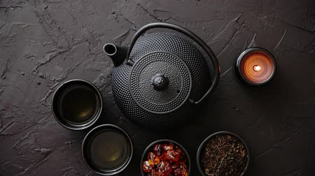 chaleira : Traditional japanese or chinese herbal tea recipe prepared in cast iron teapot with organic dry herbs. Above view on black stone background. Vídeos
