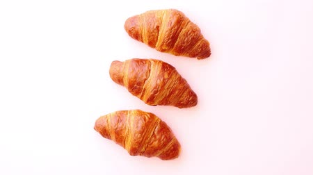 tereyağlı : Row of three fresh and delicious croissants isolated on pastel pink background. Top view with copy space.