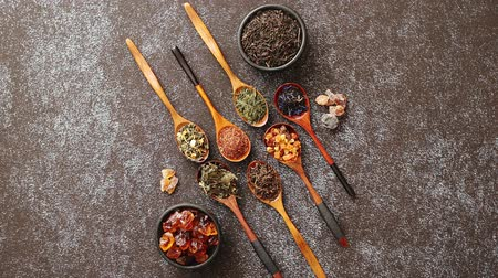 various tea : Spoons with different types of dry tea leaves on rusty dark background. Top view. Stock Footage
