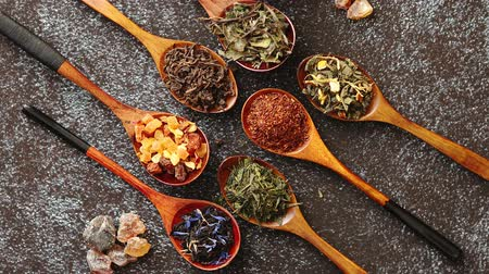 hibiscus : Spoons with different types of dry tea leaves on rusty dark background. Top view. Stock Footage