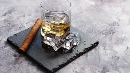 slate : Glass of whiskey with ice cubes and cigar placed on top of stone serving plate. Stone marble background.