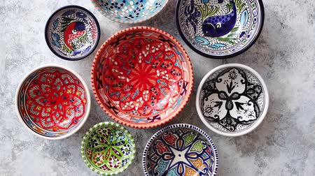 porcelana : Collection of empty moroccan colorful decorative ceramic bowls. Composition captured from top view, flat lay. Placed on grey stone background. Stock Footage