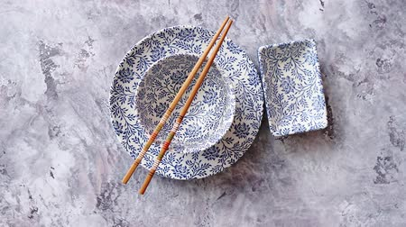 Çin yemek çubukları : Empty traditional set tableware from Asia. Chopsticks, bowl, plate and soy souce dish placed on stone background with copy space.