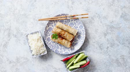 капуста : Orginal asian deep fried spring rolls placed on beautiful oriental style plate with chopstick, boiled rice, cucomber nad hot chilli peppers od side. Top view on stone background.