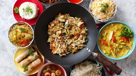 wok food : Asian oriental food composition in colorful dishware, served on stone, top view. Chinese, vietnamese, thai cuisine set. With copy space Stock Footage