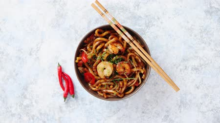 câmara : Traditional asian udon stir-fry noodles with shrimp in bowl and chopsticks. Fresh chilli pepers on side. Placed on bright stone background with copy space.