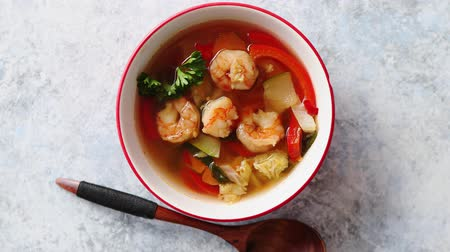 yum yum : Traditional Tom Yum spicy Thai soup with shrimp, seafood, coconut milk and chili pepper in served red bowl. Fresh chilli pepper and wooden spoon on sides. Top view with copy space.